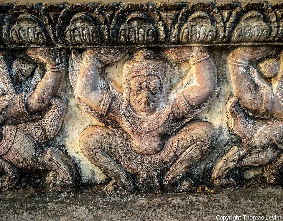 Engravings of monkeys on the temple wall in a Prasat Rolos. iPhone.