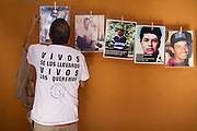 A member of Fuerzas Unidas por Nuestros Desaparecidos en Coahuila (FUNDEC), a local organization dedicated to disappeared people in this northern state holds pictures in a wall in Saltillo, on October 21st, 2012 (Photo: Prometeo Lucero)