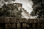 The west side of the Kukulkan Pyramid (El Castillo) from over the wall of the Platform of the Skulls (Tzompantli) at the Chichen Itza world heritage site, Yucatan, Mexico