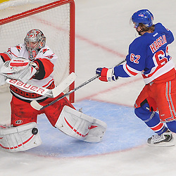 New York Rangers left wing Carl Hagelin (62) deflects the puck under Carolina Hurricanes goalie Cam Ward's (30) catching glove during first period NHL action between the Carolina Hurricanes and the New York Rangers at Madison Square Garden in New York, N.Y.