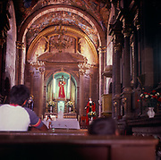 A294K2 People praying looking towards the altar church interior Mexico