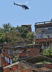 Um helicóptero da polícia militar sobrevoa a favela Morro do Alemão em 28 novembro de 2010 no Rio de Janeiro, Brasil. Após dias de preparação, forças de segurança do Brasil, lançaram um ataque contra uma favela, onde entre 500 e 600 traficantes de drogas estão escondidos e recusam a se render. Cerca de 2.600 tropas aerotransportadas, marines e membros das unidades de elite da polícia participaram da operação como alvo um grupo de favelas sem lei conhecido como Complexo de Alemão. FOTO: Jefferson Bernardes/Preview.com