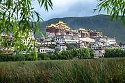 Songzanlin Tibetan Buddhist Monastery reflected in sacred lake, Shangri-La, Yunnan Province, China