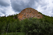 VILDMARKSVÄGEN JULI 2020<br /> Röberg passeras under helgens tur efter Vildmarksvägen ner mot Saxnäs.<br /> Sägnen gör gällande att Röberg var ättestupa för de samer som inte orkade följa med på de årliga rajderna och att blodet från de avlidna gett klippan dess röda färg.<br /> Syns bäst på eftermiddagen då berget riktigt glöder.<br /> Foto: Per Danielsson/Projekt.P