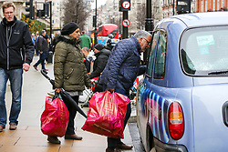 © Licensed to London News Pictures. 23/12/2018. London, UK. A couple with shopping bags speaking with a taxi driver on Oxford Street. Last minute Christmas shoppers take advantage of pre-Christmas bargains in London's Oxford Street. Fewer shoppers have been reported shopping in Britain's high streets as online sales increase. Photo credit: Dinendra Haria/LNP