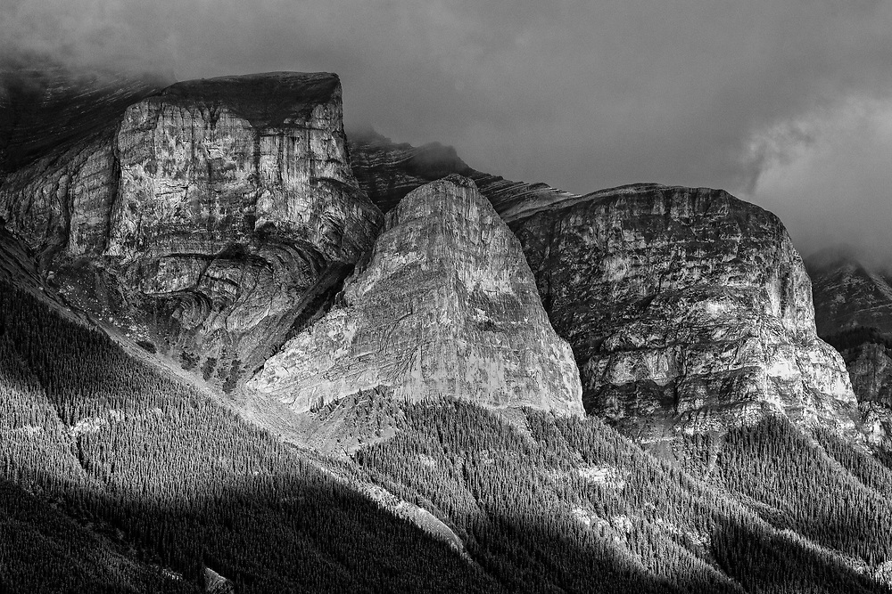 While staying in Canmore during a family vacation, I awoke early one morning and took a walk on a paved pathway with my camera. The light on the Rundle set of mountains was beautiful and of course I made a few images with a longer lens. This image looked much better as a black and white photograph when converted. There was also a lifting fog over the mountains in the morning light, which added to the drama.