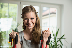 Portrait of a young woman exercising in living room, Munich, Bavaria, Germany