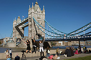 Girls jump in the air for their selfie beneath Tower Bridge on the river Thames, on 26th September 2018, in London, England.