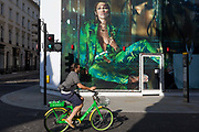 With a further 184 reported UK Covid deaths in the last 24 hrs, a total now of 43,414, a cyclist riding a Lime.E rental bike pedals beneath a billboard during the construction of a new Versace store on New Bond Street during the Covid pandemic lockdown, now easing after three months of the Stay At Home policy but now being relaxed as the shops re-open, on 26th June 2020, in London, England. Government restrictions on the 2 metre rule is to be realxed on 4th July and replaced with one metre plus in the hope it stimulates the struggling UK economy.