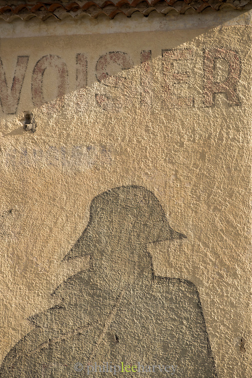 Painted on facade and faded advert for Courvoisier Cognac with Napoleon silhouette, France