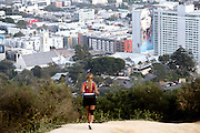 A woman is running inside Franklin Canyon Park, standing on a hill above Los Angeles looking towards Beverly Hills, California, USA.