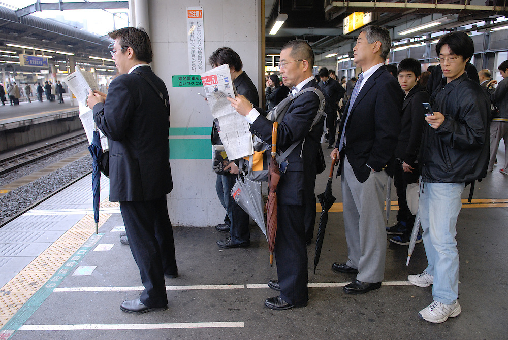 Commuters wait on the platform. One man has rucksack on back to front. Tokyo has one of the most extensive and efficient transport networks in the world - but also one of the most crowded. Rail companies calculate crowding by percent of standard capacity (ie when all the seats and standing spaces are occupied). Some trains reach 220%+.