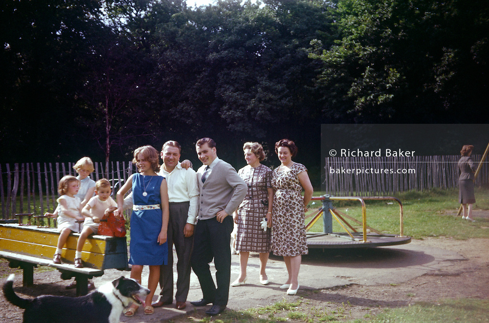 Families and friends have their photo taken in a childrens' playground in the early nineteen sixties.