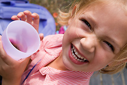 Portrait of little girl laughing holding a drink,