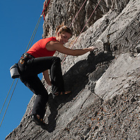 Sasha Ruttan rock climbs on Rundle Rock near town of Banff in Alberta's Banff National Park, Canada.
