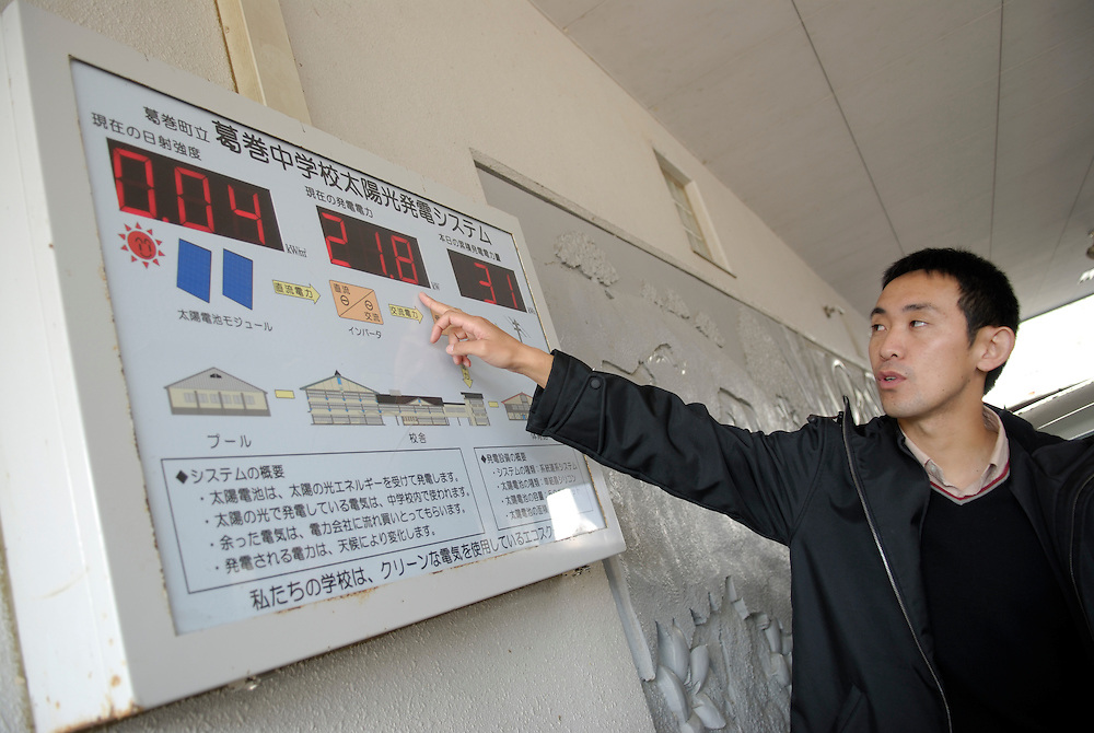"""Haruki Yoshizawa points at a display showing the rate of power generation from the solar panels at Kuzumaki Junior High School. Kuzumaki in Northern Japan bills itself as a town of """"Milk, wine and clean energy"""". The 8000 population town has little local industry so Kuzumaki invited Japanese companies to set up wind, solar and biogas generating plants."""