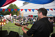 People gathering to hang out, listen to bands and other activities at the Blue Ribbon Village. Band performs on stage. Totally Thames takes place over the whole month in September, combining arts, cultural and river events presented by Thames Festival Trust throughout the 42-mile stretch of the River Thames in London, UK.