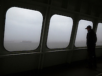 A Washington State Ferry passenger looks out a window at the rain and Seattle while crossing Puget Sound, Washington, USA