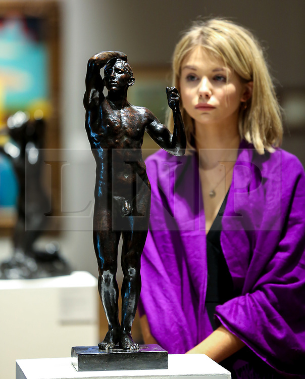 © Licensed to London News Pictures. 25/02/2019. London, UK. A woman views L'Age d'airain (The Age of Bronze) sculpture by Rodin. Estimate: £100,000-150,000. Conceived between 1875-1877, L' Age d'airain caused great controversy when it was first shown. The figure was so intensely realistic that critics initially refused to believe Rodin had not simply made a cast of his model.<br /> Bonhams Impressionist and Modern Art Sale will take place in London on 28 February 2019. Photo credit: Dinendra Haria/LNP