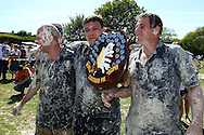 Coxheath, Kent - Saturday, May 22nd 2010: Karl Hickmott (centre) of the High Pressure Cleaning Company holds the World Custard Pie Trophy after his team beat the Coxheath team 96-56 in the final at the World Custard Pie Championships at Coxheath near Maidstone, Kent. The first championship was held in 1967 in Coxheath using a special custard recipe developed by Richard Hearn aka Mr Pastry. The championship is made up of teams competing in heats, semi finals and the final, with the number of pies available per team increasing from 5 in the heats to 10 in the final. 6 points are scored for a direct hit on the face, 3 points for the shoulders or upwards, 1 point for any other part of the body, and points are deducted for misses. A discretionary 5 points can be awarded for the most amusing and original throwing technique. The event is part of the Rotary Club funday. (Pic by Andrew Tobin/SLIK Images)