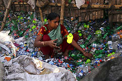 October 1, 2018 - Dhaka, Bangladesh - Female laborers sort through polyethylene terephthalate (PET) bottles in a recycling factory at Mohammadpur in Dhaka, Bangladesh, 01 October 2018. Recycling plastic bottles has become a growing business over the last couple of years as well as helping to protect the environment. According to the Bangladesh PET Flakes Manufacturers and Exporters Association (BPFMEA), Bangladesh exports on an average nearly 30,000 tons of PET bottle flakes mainly to China, South Korea and Taiwan worth $14 million dollars per year. (Credit Image: © Kazi Salahuddin Razu/NurPhoto/ZUMA Press)