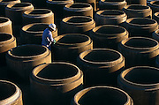 """Precast concrete pipes are prepared for distribution by a Mexican-born employee at Hanson Pipe & Products, Grand Prairie, Texas, USA. He cleans and inspects the tongue and groove seals of the upturned pipes wearing an obligatory hard hat and blue overalls. Precast concrete is made from a reusable mold or """"form"""" and cured in a controlled environment, then transported to the construction site and lifted into place. Used in the construction of commercial building components, bridges, manholes and retaining walls, these products are the strongest pipe available, designed and plant tested to resist any load required with a design life of 70-100 years. .."""