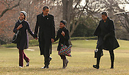 President Barack Obama and First Lady Michelle Obama and daughters Sasha and Malia walk from marine One to the White House upon their return to Washington from a Christmas holiday vacation in Hawaii.  Photograph by Dennis Brack