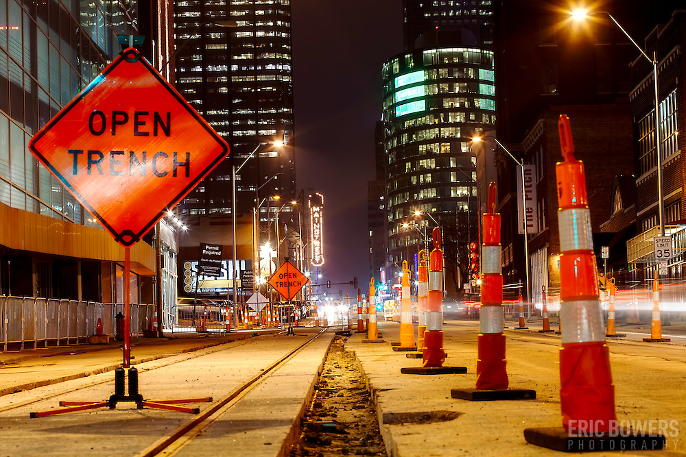Low angle photo with view up Main Street in downtown Kansas City Missouri from about 17th Street; construction progress underway for the Kansas City streetcar line. Early evening after sunset.