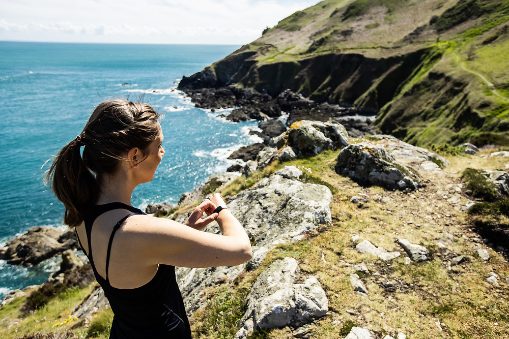 Woman enjoying a healthy active lifestyle, out for a run on the north coast cliff paths in Jersey, Channel Islands, stopping to check her Fitbit