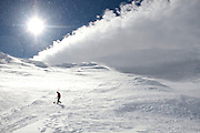 Ski patroller walking through swirling snow in high winds near the summit of active volcano Mount Ruapehu, New Zealand.