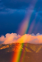 A rainbow with large puffy clouds and the Santa Ynez Mountains in background, Santa Barbara, California USA.