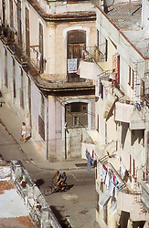 View looking down onto Havana street with washing; balconies and cyclists,