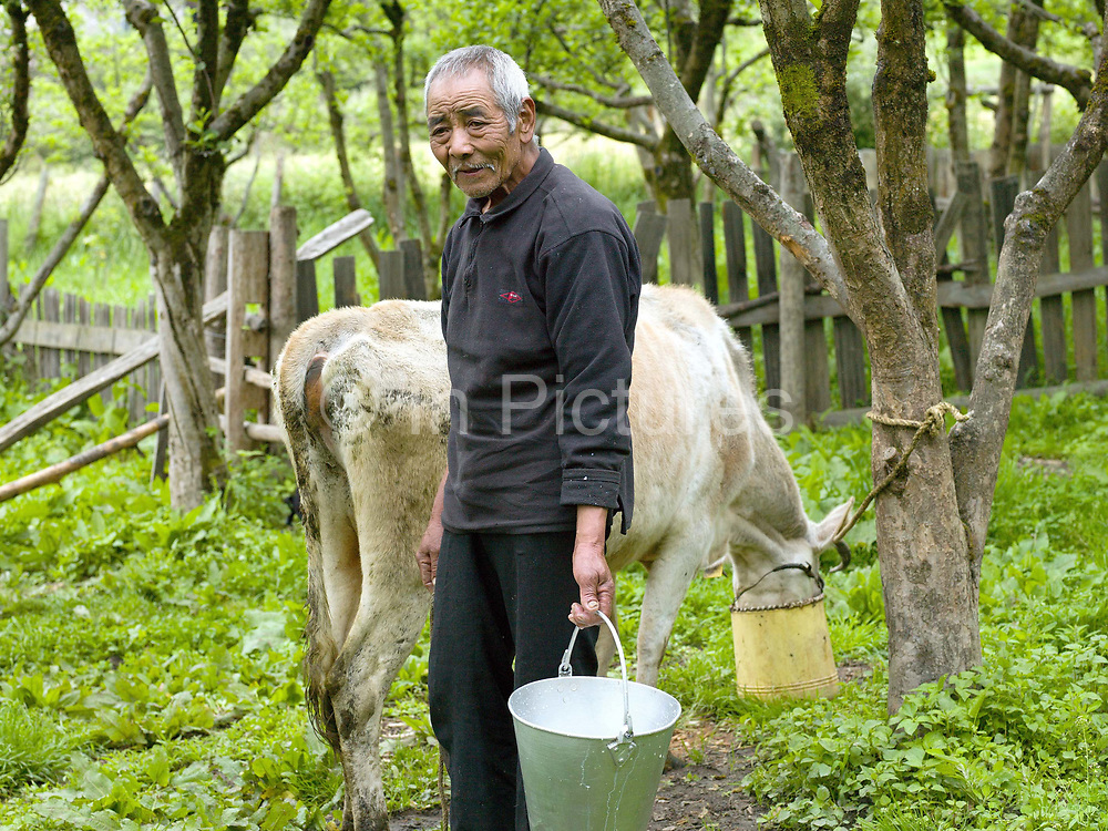 Portrait of smallholder/farmer Karma holding a bucket of milk after hand milking one of his 11 cows in the Tang Valley, Bumthang, Central Bhutan. Rural Bhutanese farmers make butter and cheese partly for storage or as a preserved form of milk for self consumption, with any excess being sold for cash.
