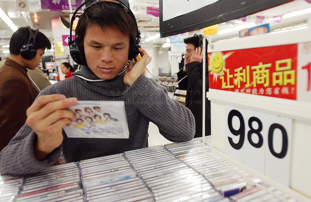 DONGGUAN, GUANGZHOU, CHINA- FEB 9:  People listen and look over the CD selections while shopping at the Wal Mart Store on February 9, 2004 in Dongguan, Ghangzhou, China.  Photograph by David Paul Morris
