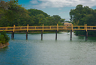 A painting -like photo of Spring Lake bridge surrounded by green trees, with a blue sky background reflected in the lake, and a glimpse of the town in the background.