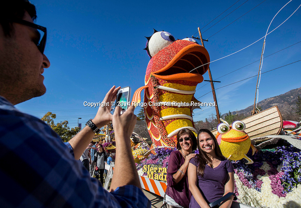 """Floats viewers take pictures with theSierra Madre Rose Float Association float """" Catching the Big One"""" during the 125th Rose Parade's Showcase of Floats on Thursday, January 2, 2014 in Pasadena, California. (Photo by Ringo Chiu/PHOTOFORMULA.com)"""