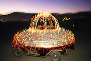 Flying saucer golf cart at Burning Man. Burning Man is a performance art festival known for art, drugs and sex. It takes place annually in the Black Rock Desert near Gerlach, Nevada, USA..An art car decorated in colored lights as a flying saucer at Burning Man, the art, drugs and sex festival held annually in the Black Rock Desert near Gerlach, Nevada, USA.