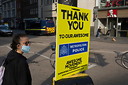 With the Coronavirus lockdown continuing into the Bank Holiday weekend, when Prime Minister Boris Johnson is due to tell the nation that only a gradual easing of regulations and social distancing rules are still to be in place, a person wearing a surgical mask prepares to cross Bishopsgate where a sign that supports emergency services workers such as the police has been attached to a crossing post in the City of London, the capital's financial district, on 7th May 2020, in London, England.