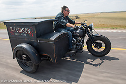 RJ Gibson on his Panhead sidecar rig with his tintype darkroom rig riding north on highway 79 on the Run to the Line for lunch and biker vs Cowboy rodeo games at the Spur Creek Ranch in Newell during the annual Sturgis Black Hills Motorcycle Rally. SD, USA. Wednesday August 9, 2017. Photography ©2017 Michael Lichter.