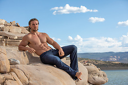 hot man without a shirt in jeans relaxing on a rock formation by a lake