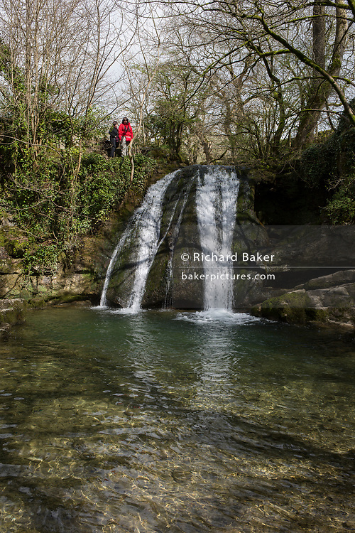 Walkers admire the Yorkshire Dales waterfall called Janet's Foss on 12th April 2017, in Malham, Yorkshire, England. Janet's Foss is a small waterfall in the vicinity of the village of Malham, North Yorkshire, England. It carries Gordale Beck over a limestone outcrop topped by tufa into a deep pool below. The pool was traditionally used for sheep dipping, an event which took on a carnival air and drew the village inhabitants for the social occasion. The name Janet (sometimes Jennet) is believed to refer to a fairy queen held to inhabit a cave at the rear of the fall. A foss is an old Norse word meaning waterfall.