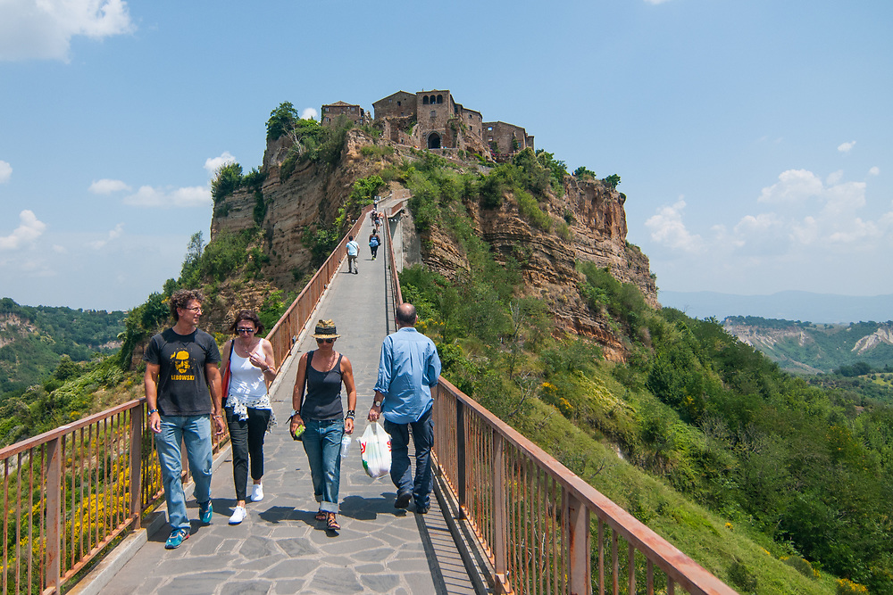 """Tourists and citizen cross the bridge that leads to the village of Civita di Bagnoregio.<br /> Civita di Bagnoregio is a town in the Province of Viterbo in central Italy, a suburb of the comune of Bagnoregio, 1 kilometre (0.6 mi) east from it. It is about 120 kilometres (75 mi) north of Rome. Civita was founded by Etruscans more than 2,500 years ago. Bagnoregio continues as a small but prosperous town, while Civita became known in Italian as La città che muore (""""The Dying Town""""). Civita has only recently been experiencing a tourist revival. The population today varies from about 7 people in winter to more than 100 in summer.The town was placed on the World Monuments Fund's 2006 Watch List of the 100 Most Endangered Sites, because of threats it faces from erosion and unregulated tourism."""