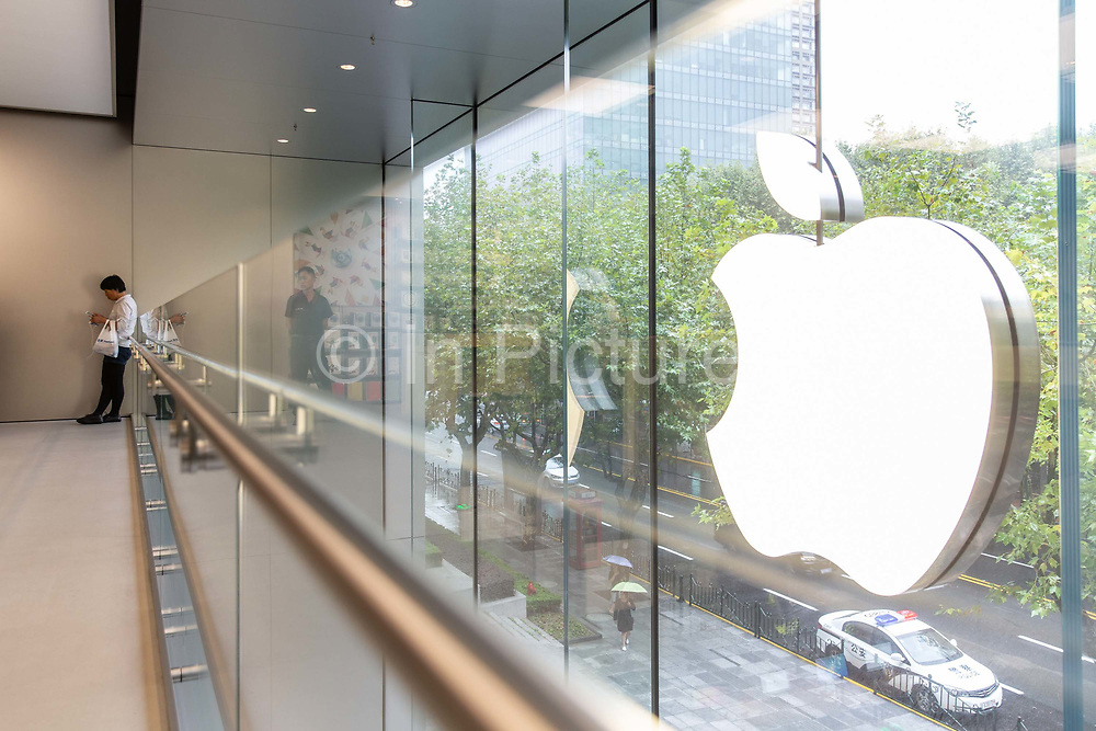 A woman stands at the Apple Store inside the IAPM shopping mall in Shanghai, China, on Friday, Sept. 16, 2016. iPhone sales are slowing in Chinas Apples second largest market, as local upstarts such as Huawei and Xiaomi are eating into the companys high end market.