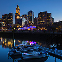 Boston North End Christopher Columbus Waterfront Park night photography from New England Photography Guild member and award winning fine art photographer Juergen Roth showing Boston Custom House of Boston, the waterfront and parts of the Columbus Park and Boston Marriott Long Wharf hotel. The Boston skyline was photographed on a beautiful spring sunset. <br />