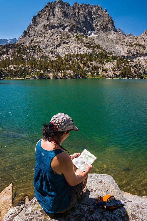 Hiker reading map on the shore of Big Pine Lake #5, John Muir Wilderness, Sierra Nevada Mountains, California USA