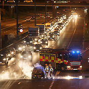 Fire crews attend to a car fire on M8 at Cranhill, Glasgow.  Picture Robert Perry 10th Sept 2015<br /> <br /> Must credit photo to Robert Perry<br /> FEE PAYABLE FOR REPRO USE<br /> FEE PAYABLE FOR ALL INTERNET USE<br /> www.robertperry.co.uk<br /> NB -This image is not to be distributed without the prior consent of the copyright holder.<br /> in using this image you agree to abide by terms and conditions as stated in this caption.<br /> All monies payable to Robert Perry<br /> <br /> (PLEASE DO NOT REMOVE THIS CAPTION)<br /> This image is intended for Editorial use (e.g. news). Any commercial or promotional use requires additional clearance. <br /> Copyright 2014 All rights protected.<br /> first use only<br /> contact details<br /> Robert Perry     <br /> 07702 631 477<br /> robertperryphotos@gmail.com<br /> no internet usage without prior consent.         <br /> Robert Perry reserves the right to pursue unauthorised use of this image . If you violate my intellectual property you may be liable for  damages, loss of income, and profits you derive from the use of this image.