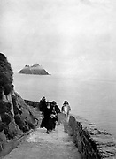 The Skelligs Rocks boat trip in the 1940's was not for the faint hearted.  Seven boats would carry up to 50 people in each boat with no life jackets accross chjoppy seas the 7 miles out in open sea to Skellig Michael.  The pathways were overgrown and the beehive huts were in the same state as they were when St. Finan founded his monastery which was vacated in the 13th century. Mass has been celebrated by locals since the 16th century and in the 1940's our founding father Daniel MacMonagle accompanied the 'pilgrims' on their annual Mass trip in late September to capture these historic photographs showing the local priest leading the adventure.<br /> Photo: Daniel MacMonagle - macmonagle.com