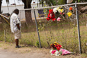 A passerby stops to view the makeshift memorial marking the spot where unarmed black motorist Walter Scott was gunned down by police following a traffic stop April 10, 2015 in Charleston, South Carolina. Scott was shot multiple times in the back and died on the scene after running from police.