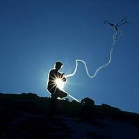 ROCK CLIMBING. John Fischer (MR) throwing a rope off Buttermilk Rocks, Sierra Nevada, near Bishop, CA.