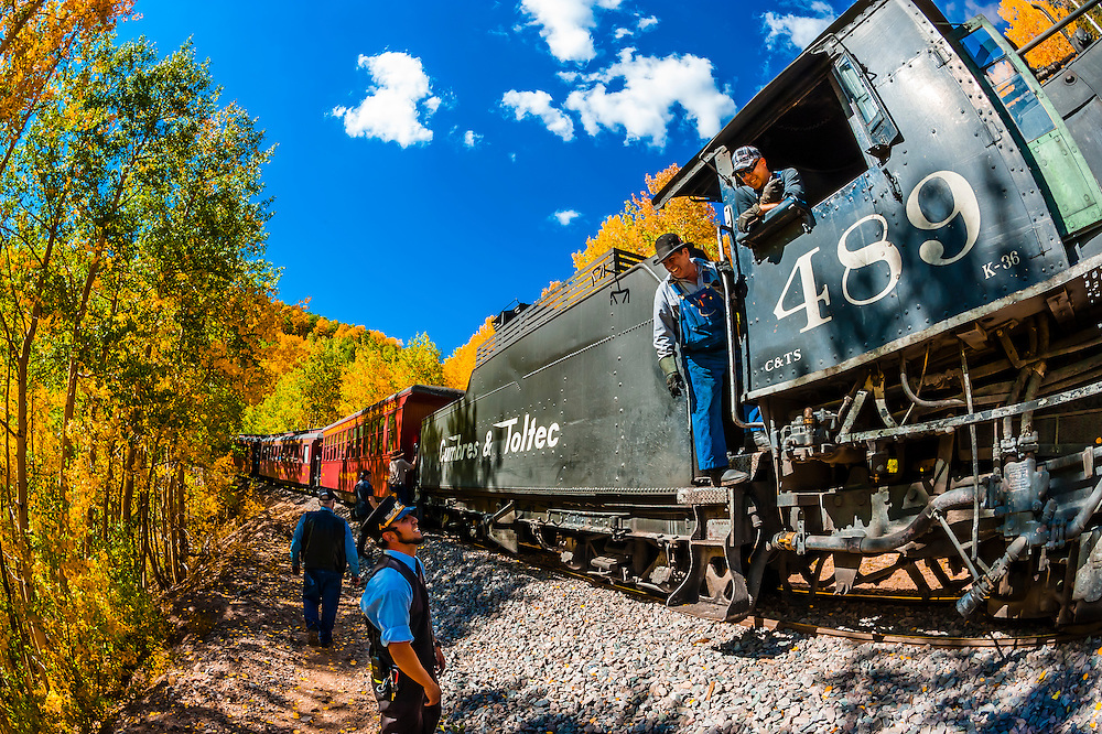 A brief stop near Calico, CO, surrounded by a grove of aspen trees in peak autumn color on the Cumbres & Toltec Scenic Railroad train on the 64 mile run between Chama, New Mexico and Antonito, Colorado. The railroad is the highest and longest narrow gauge steam railroad in the United States with a track length of 64 miles. The train traverses the border between Colorado and New Mexico, crossing back and forth between the two states 11 times. The narrow gauge track is 3 feet wide. It runs over 10,015 ft (3,053 m) Cumbres Pass.